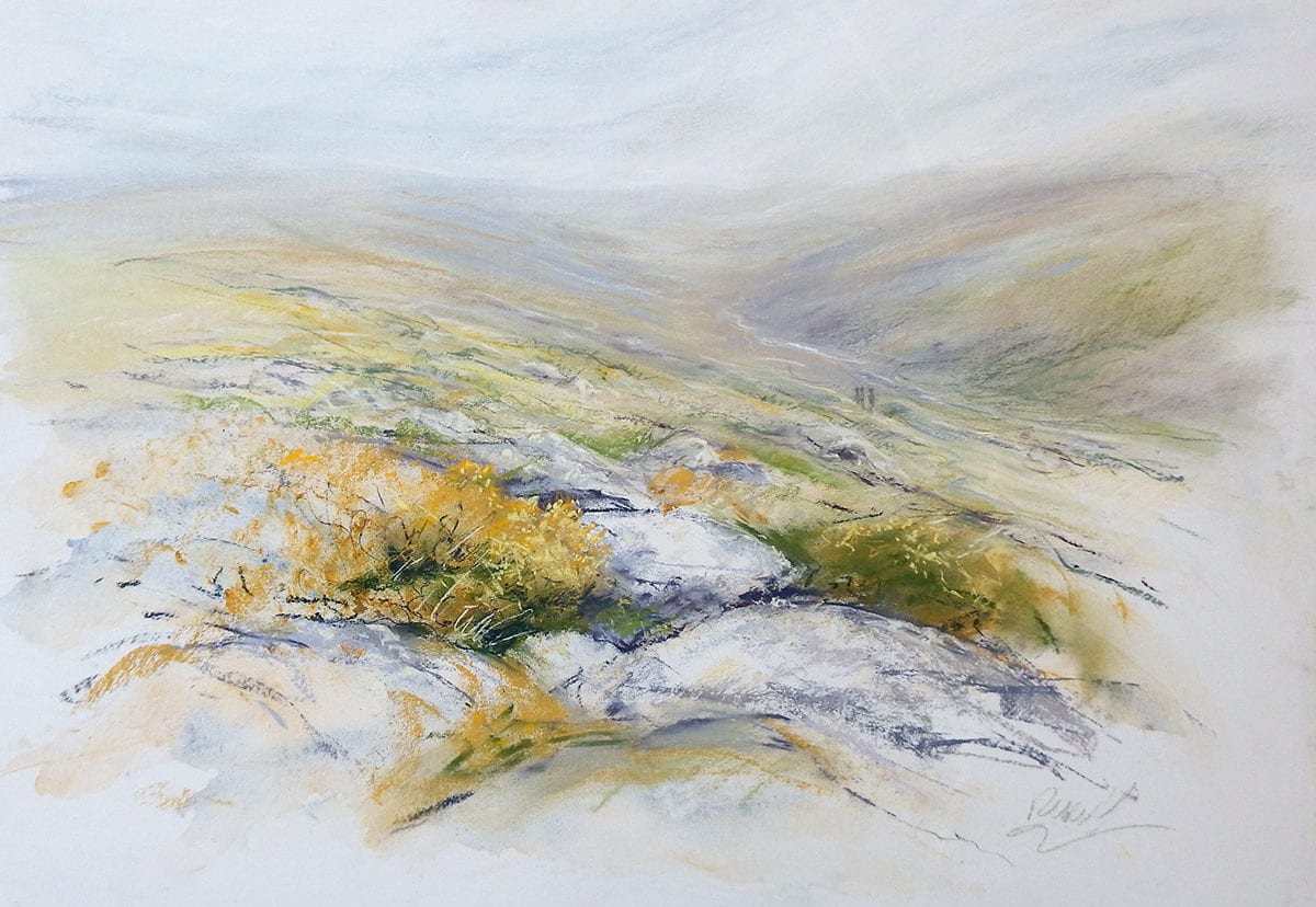 An original pastel painting of a misty, rainy day on Dartmoor in Devon. Tiny figures can be seen hiking along a path, dwarfed by the huge landscape, walking down the valley where a stream glints in the light. In the foreground a group of lichen-covered rocks are surrounded by gorse and heather. The colours are pale and soft, with grey and lilac, and greens and yellows of the plants.